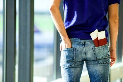 Closeup passports and boarding pass in the pocket of jeans at airport